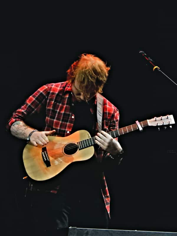 Ed Sheeran playing guitar on stage with a capo