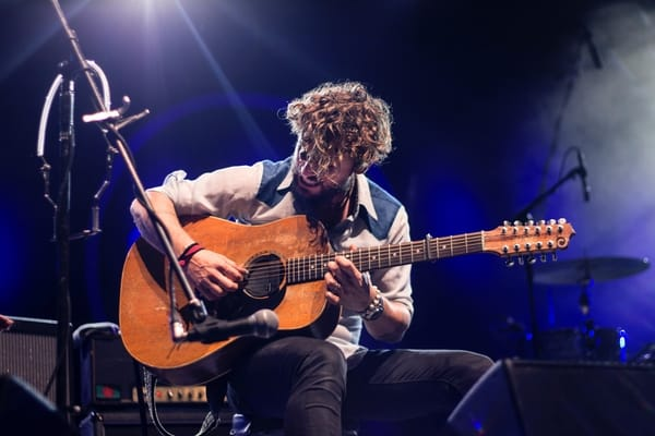 man using a capo in a concert
