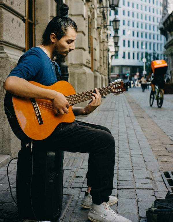 busker playing guitar with a barre chord