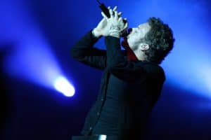 Chris Martin singing on stage with a blue background