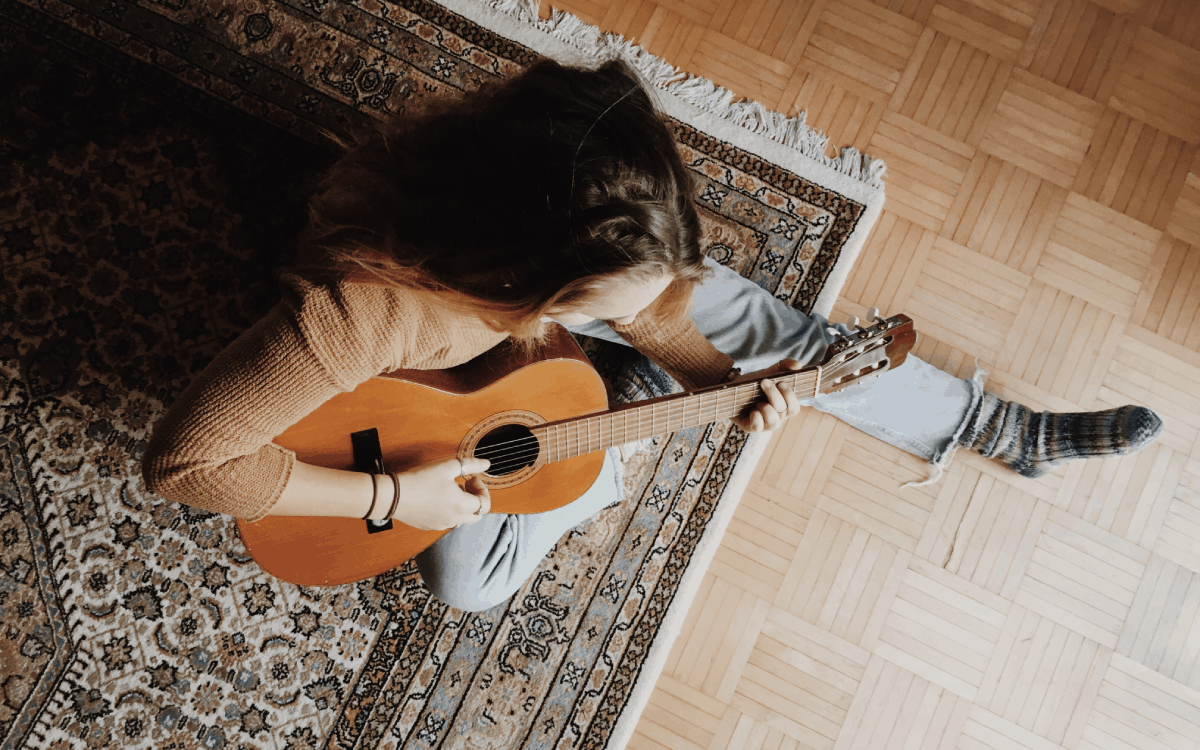 Lady playing classical guitar sitting on a rug