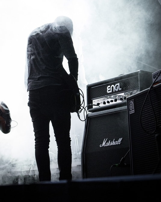 guitarist on stage with a guitar amplifier