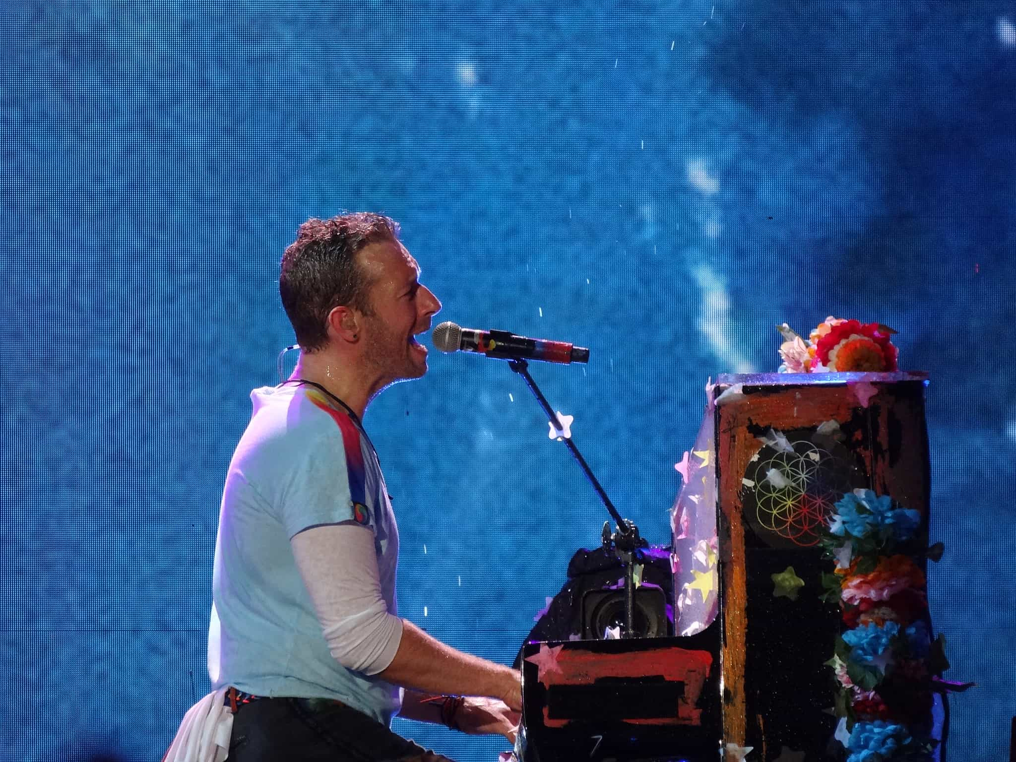 Chris martin playing piano and singing on stage