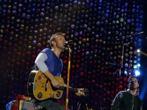 Chris Martin singing on stage with a guitar
