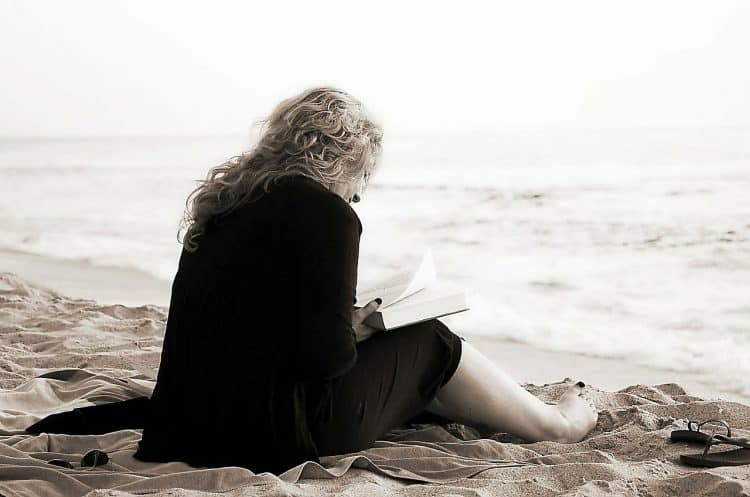 person reading a book on the beach taking a lot of time