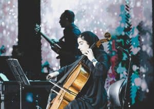 Cellist playing with a bow on stage.