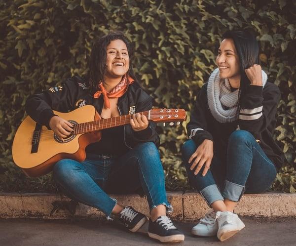 two women having fun one is strumming a guitar