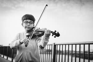 Boy playing violin after breaking down the music
